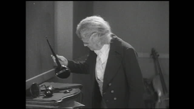 old man writing sheet of music on the desk with a quill pen and handing it to the younger man when finished; younger man reads the music while older... - 1940 1949 stock-videos und b-roll-filmmaterial