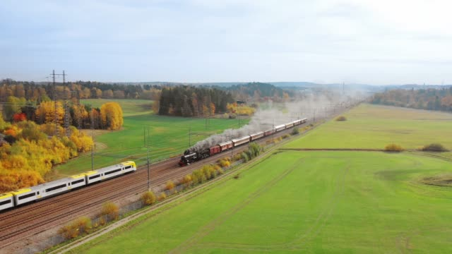 old meets new, steam train crosses agricultural fields, new trains passing each side - history stock videos & royalty-free footage
