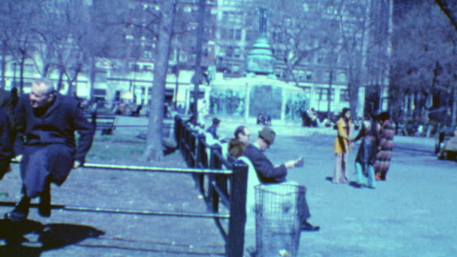 old men reading newspaper on park bench / young african american women dancing / liberty pole flagstaff gifted by charles meyers is visible in the... - union square new york city stock videos and b-roll footage