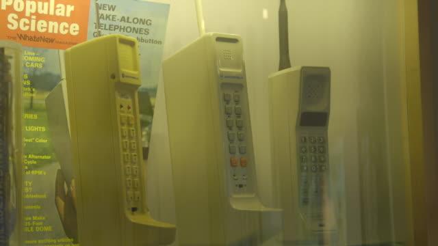 old mobile motorola phones on display, close-up - skåp med glasdörrar bildbanksvideor och videomaterial från bakom kulisserna