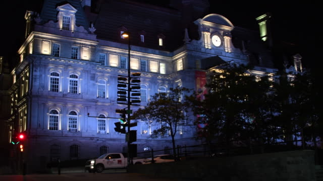 old montreal, canada: city hall facade at night with contrasting blue and yellow lights on - モントリオール旧市街点の映像素材/bロール
