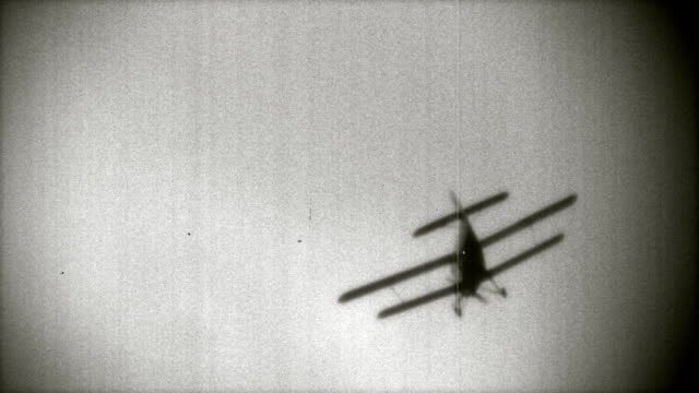 old movie effect. biplane - black and white stock videos & royalty-free footage