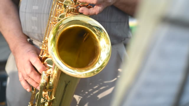 old musician is playing on saxophone in park - saxophone stock videos and b-roll footage