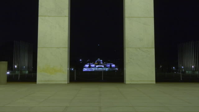 WS T/L ZO Old Parliament House and Australian War Memorial (AWM) seen through columns of New Parliament House at night / Canberra, Australian Capital Territory, Australia