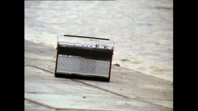 old radio sits on a paved surface beside a lake; 1971 - lakeshore stock videos & royalty-free footage