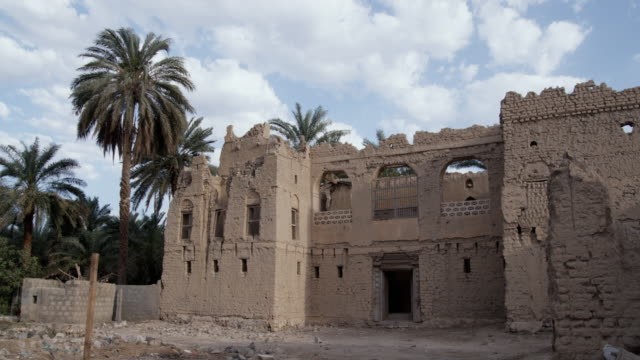 ws old ruin of mud house with palm trees blowing in wind, muscat, oman - adobe stock videos & royalty-free footage