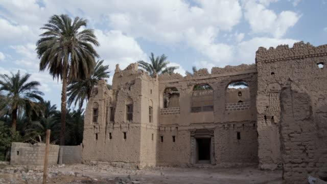 ws old ruin of mud house with palm trees blowing in wind, muscat, oman - adobe bildbanksvideor och videomaterial från bakom kulisserna