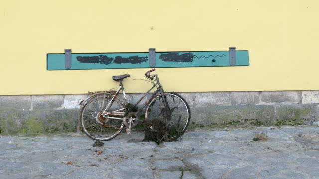 old rusty abandonned bycycle against a wall and a person walk in front of it in regensburg germany