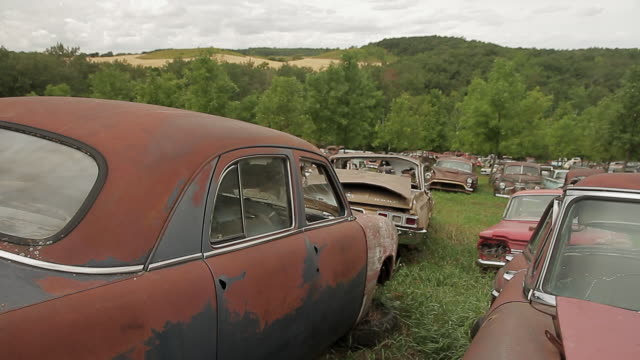 Old rusty cars in a scrap car field