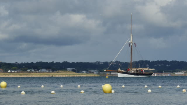 vídeos y material grabado en eventos de stock de old sailing yacht prepares to set sail with crew onboard - studland heath