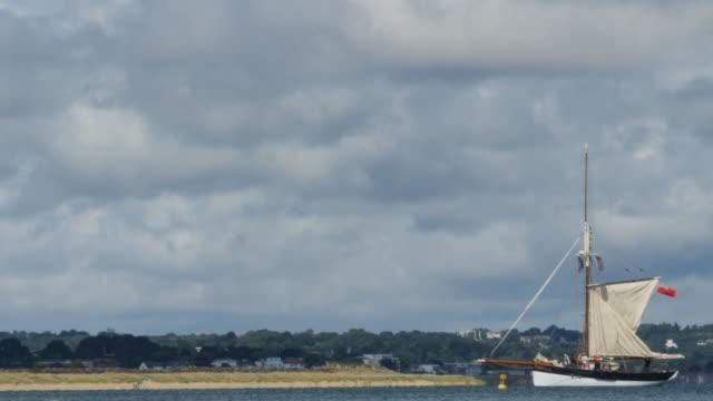 vídeos y material grabado en eventos de stock de old sailing yacht with sails up with sandy beach - studland heath
