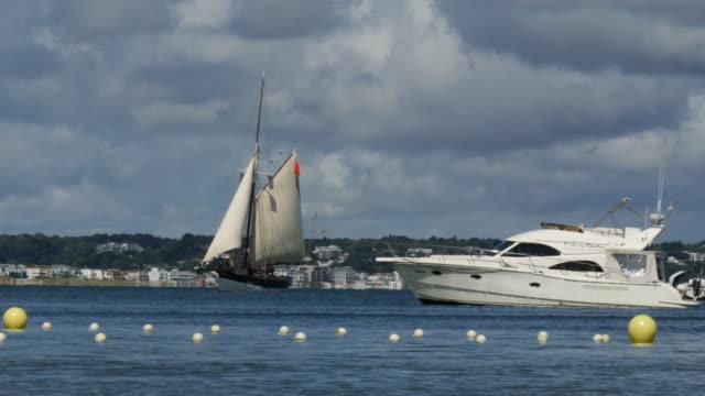 vídeos y material grabado en eventos de stock de old sailing yacht with speedboat and apartments in background - studland heath
