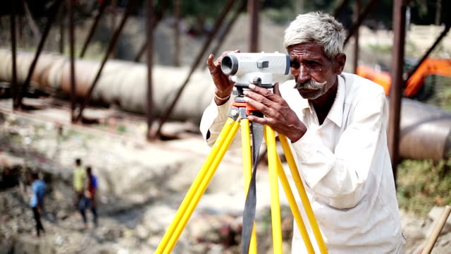 old senior man with automatic level surveyor's machine on a construction site - surveyor stock videos and b-roll footage