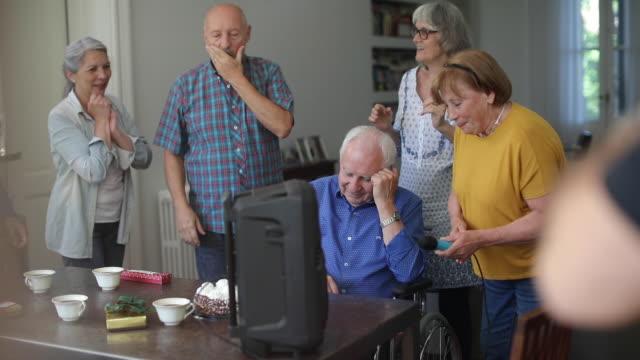 vidéos et rushes de personnes âgées âgées ayant la partie de karaoké - jeune d'esprit