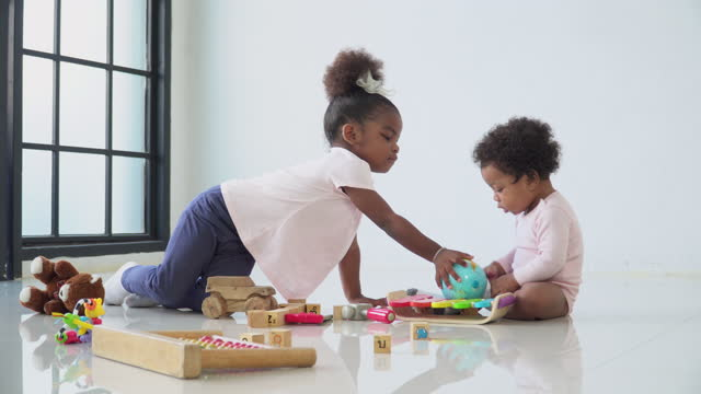 old sister sharing her world to africana baby girl, little sister, play wooden toy with innocence in the living room, concept of preschool, childhood, playing of a sibling. - 2 3 years stock videos & royalty-free footage