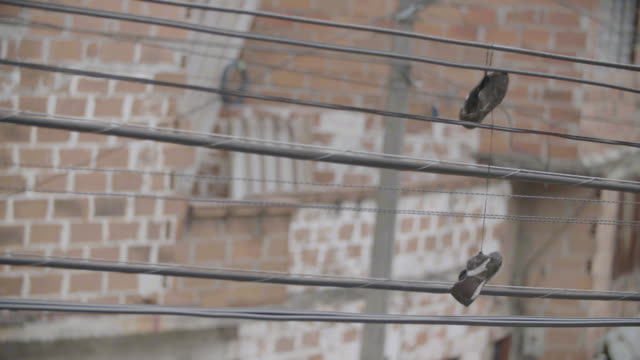 old soccer cleats, abandoned on power lines. - slum stock videos & royalty-free footage