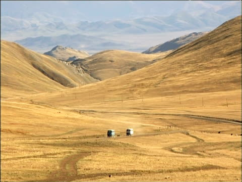 Old Soviet Army 4x4 trucks travel along dusty track in front of expanding mountain range Mongolia