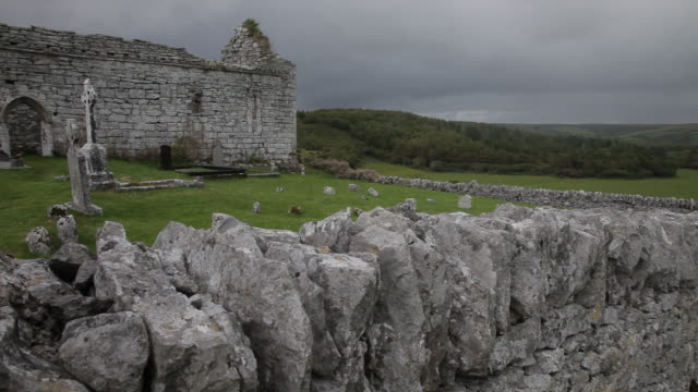 ws pan old stone building with graveyard / ireland - stone wall stock videos and b-roll footage