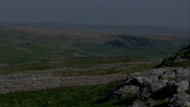 Old stone walls separate fields in a beautiful countryside. Available in HD.