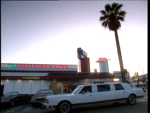 old style white stretched limo drives past exterior of hollywood diner and palm tree at dusk - 1994 stock videos and b-roll footage