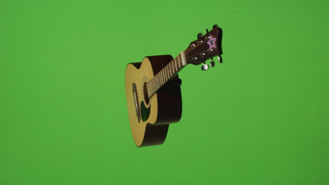 old time classic acoustic guitar hangs over green screen background. - country and western stock videos & royalty-free footage