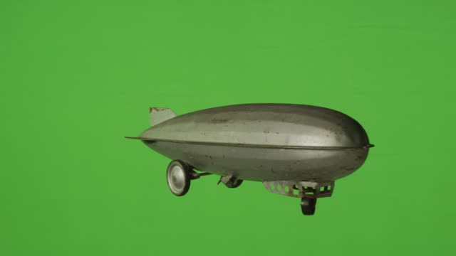 old time vintage toy blimp hangs over green screen background. - airship stock videos & royalty-free footage