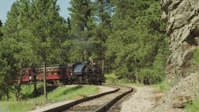 old time western steam locomotive and train chug down the railroad track toward camera round a curve in the mountains. - wild west stock videos & royalty-free footage