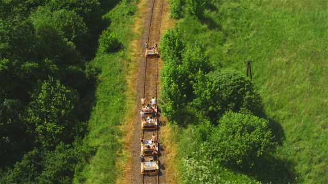 vidéos et rushes de vieux train touristique se déplaçant par la forêt de białowieża et les champs environnants. vue aérienne - transports publics