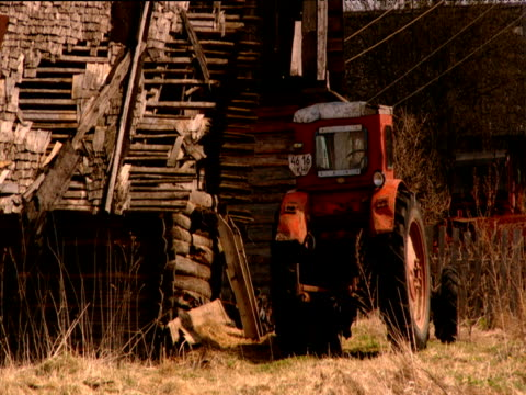 Old tractor parked by tumbledown barn Russia