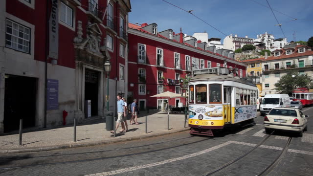 WS PAN Old tram and cars passing by Museum of Decorative Arts in in Alfama / Lisbon, Portugal