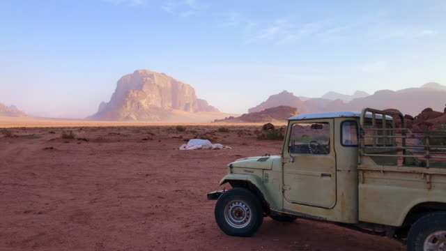 old truck in the stunning landscape of the wadi rum during sunrise. - sandstone stock videos & royalty-free footage