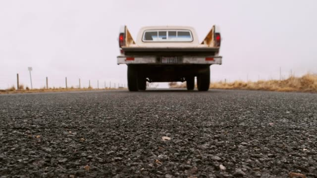 old truck on an empty road - moving past video stock e b–roll