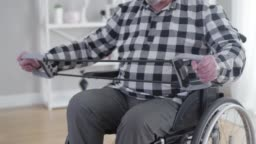 Old unrecognizable Caucasian man in wheelchair stretching elastic band. Elderly male disabled person exercising indoors. Physical therapy, health care, disability.