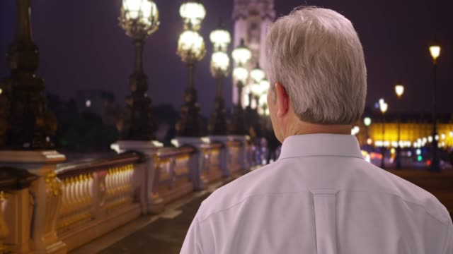 old white man travelling paris looks around city on pont alexandre bridge - pont alexandre iii stock videos & royalty-free footage