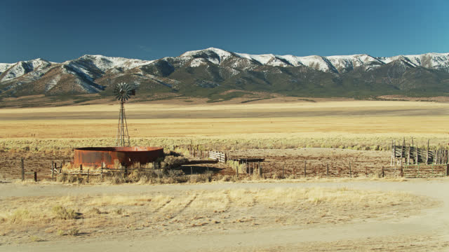 old windpump and rusty water tank with snowy hills behind - aerial - nevada stock videos & royalty-free footage