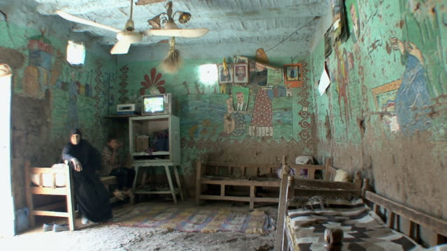ws old woman and boy inside farmer's house with frescoes of egyptian life on living room walls, kuna, egypt - ファームハウス点の映像素材/bロール