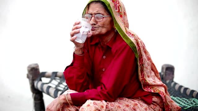Old woman drinking cold drink, time lapse