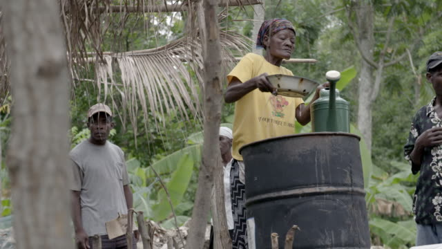 old woman filling up watering can in front of men after 2010 earthquake no - haiti stock-videos und b-roll-filmmaterial