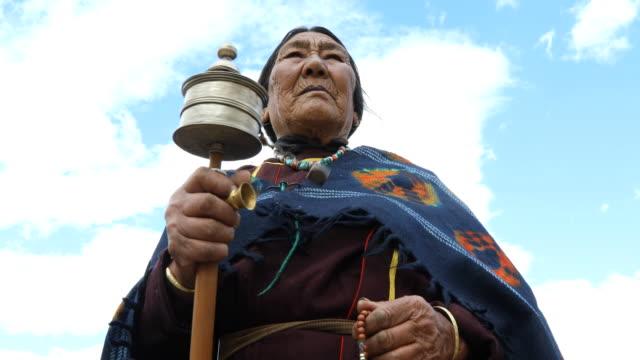 old woman holding hand prayer wheel - spiritualità video stock e b–roll