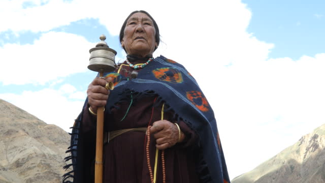 old woman holding hand prayer wheel - indigenous culture stock videos & royalty-free footage