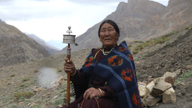 old woman holding hand prayer wheel - etnia video stock e b–roll