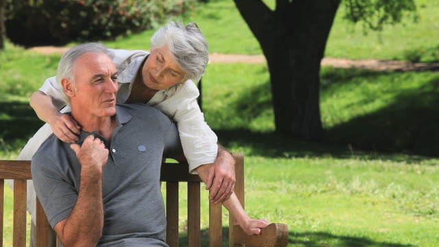 MS Old woman hugging husband on bench in Park / Cape Town, Western Cape, South Africa