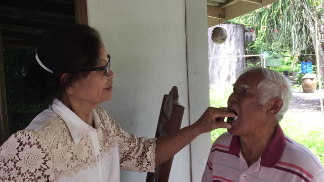 old woman inserts swab into old man's mouth after tooth extraction - tampon stock videos & royalty-free footage