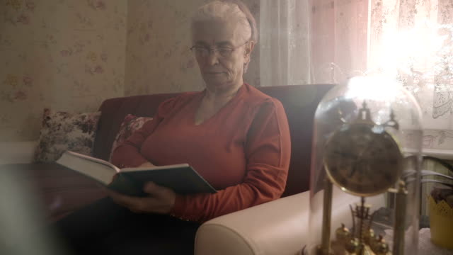old woman is reading book - wrinkled stock videos and b-roll footage