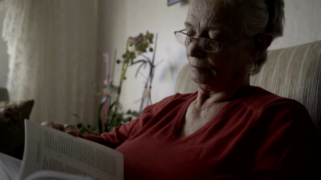 vídeos de stock e filmes b-roll de old woman is reading book - 70 anos