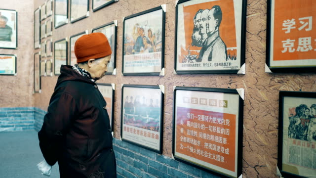 old woman looking at the propaganda pictures of the chinese cultural revolution - news event stock videos & royalty-free footage