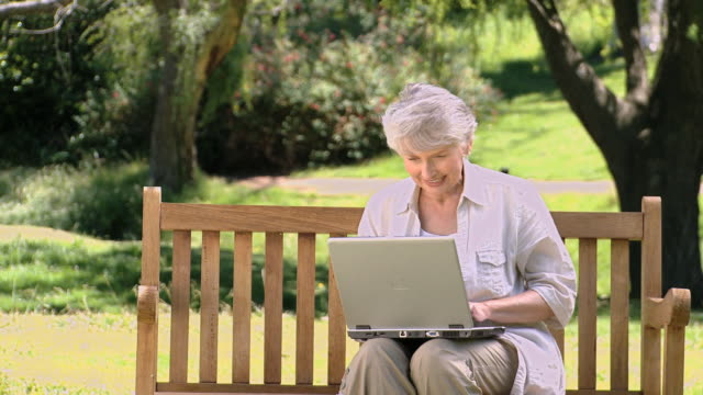 vídeos de stock, filmes e b-roll de ms td old woman sitting on bench using laptop in park / cape town, western cape, south africa - idoso na internet