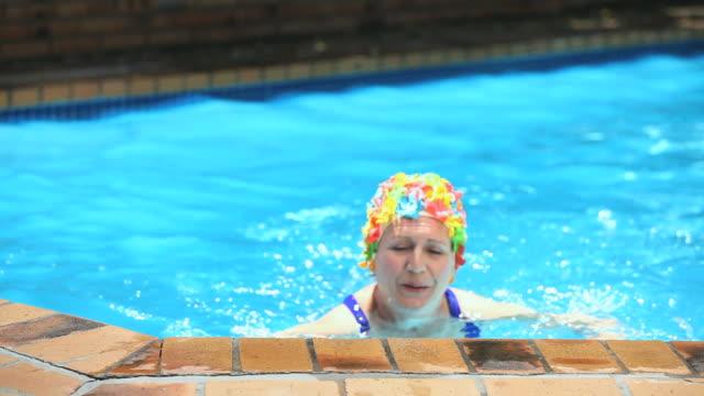 vídeos y material grabado en eventos de stock de ms old woman swimming in pool and smiling / cape town, western cape, south africa - gorro de baño