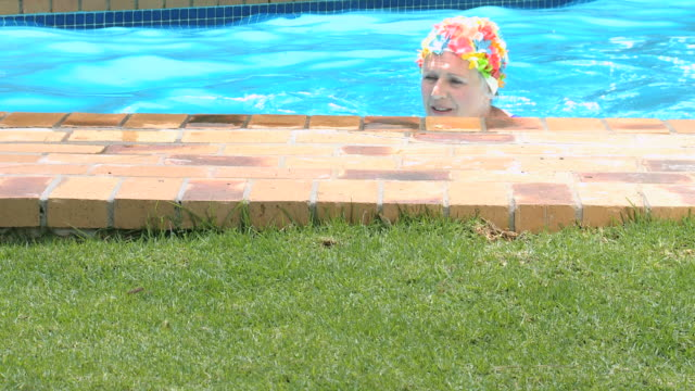 ms tu old woman swimming in pool and smiling / cape town, western cape, south africa - swimming cap stock videos and b-roll footage