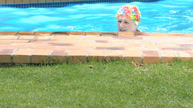 vídeos de stock, filmes e b-roll de ms tu old woman swimming in pool and smiling / cape town, western cape, south africa - touca de natação
